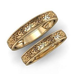 A pair of gold wedding rings with ornament